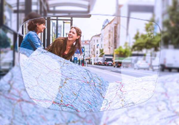 Image of two laughing woman on street and map in foreground - advertising Zeiss Varifocal lenses