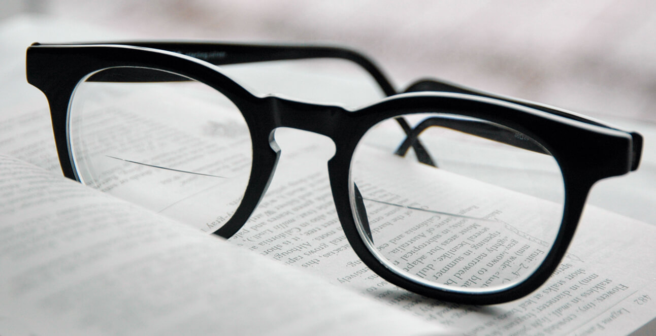 Spectacles with replacement bifocal lenses, sitting on a book
